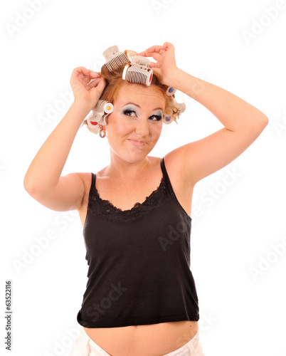 Young woman makes hair curlers.