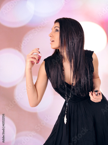 Portrait of beautiful young woman with perfume bottle.