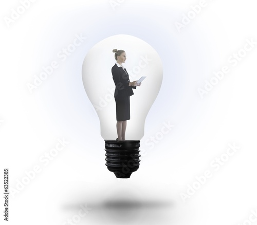 Businesswoman holding tablet in light bulb