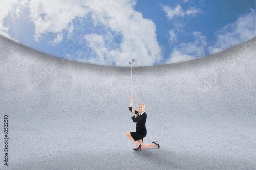 Composite image of businesswoman pulling down blue sky