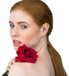 Beautiful redhead posing with red rose