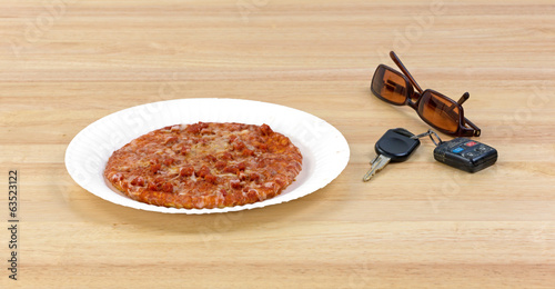 Pizza next to car keys and sunglasses