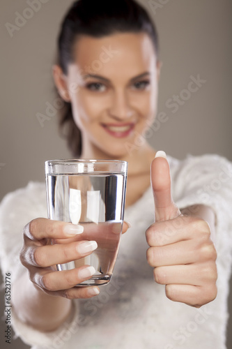 young woman holding a glass of water and showing thumbs up