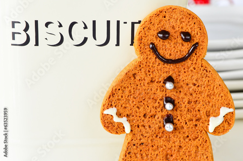 Ginger bread man standing next to biscuit tin