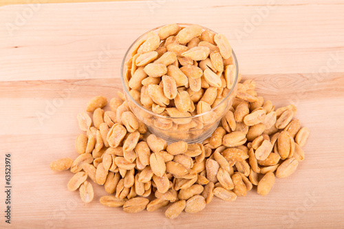 Peanuts in Glass Cup on Wood Table