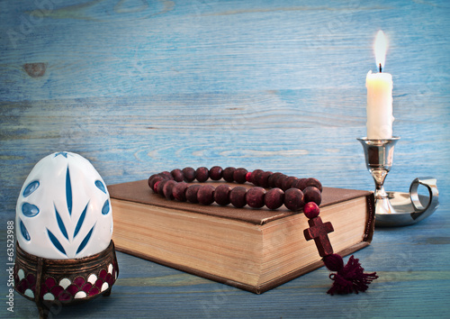 Easter egg in a stand, the Bible and candle