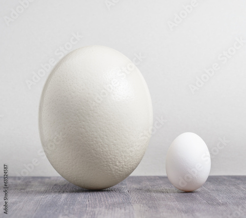 Ostrich egg and chicken egg on black table