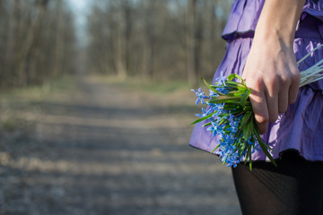 girl holding hands bouquet of blue snowdrops