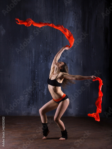 young woman with red ribbons danced   on dark modern background