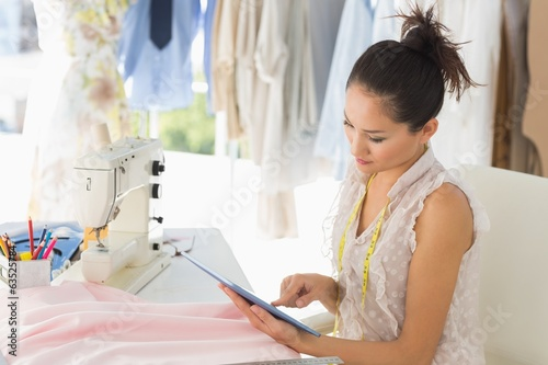 Female fashion designer using digital tablet in studio
