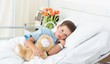 Boy lying with teddy bear in hospital - 63526113