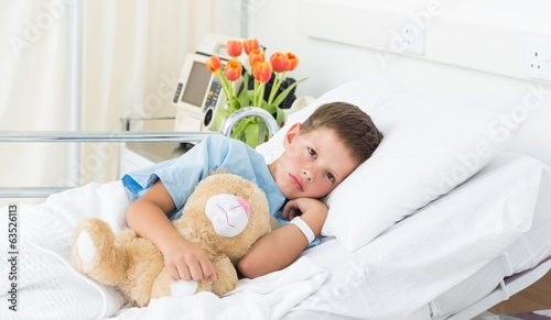 Tuinposter Ontspanning Boy lying with teddy bear in hospital