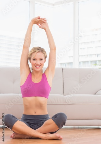 Happy blonde sitting in lotus pose stretching arms up