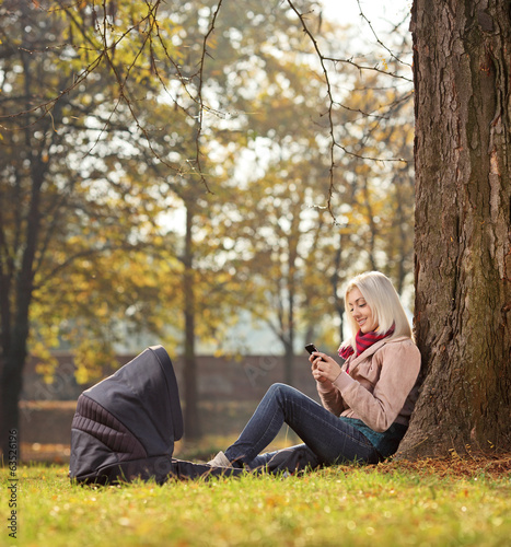 Blond girl texting by phone seated in park