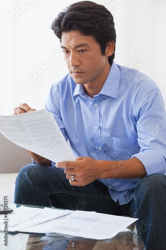 Serious man sitting on couch paying his bills