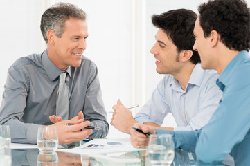 Three Businessmen Discussing In Meeting