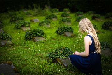 Junges Mädchen vor einem Soldatengrab