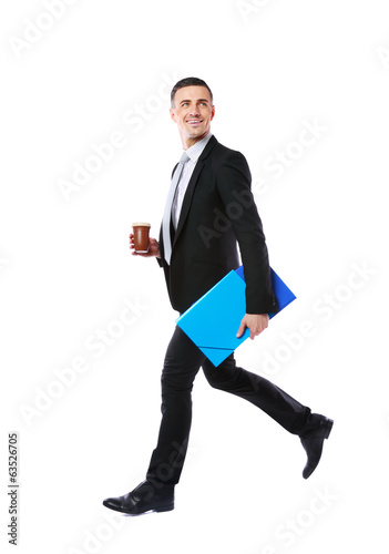 Businessman walking with blue folder and cup of coffee in hands