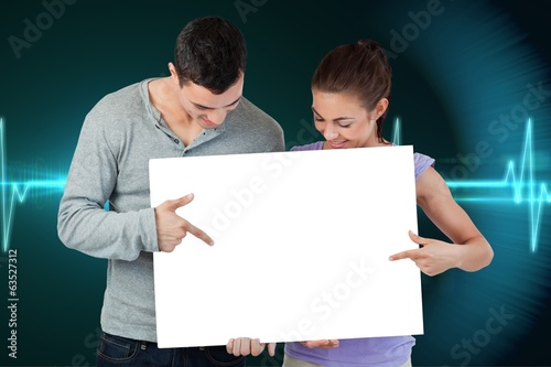 Composite image of attractive young couple showing card