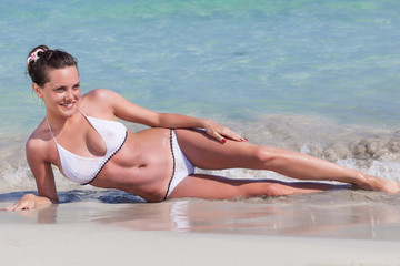 A woman is sunbathing on the beach