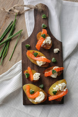 appetizer with salmon,baked potatoes and a cottage cheese