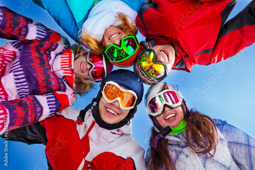 Five happy friends standing with goggles
