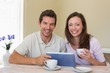 Happy couple using digital tablet while having coffee