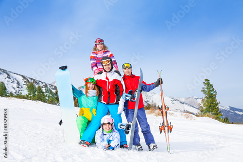 Cheerful guys standing with snowboards and skis