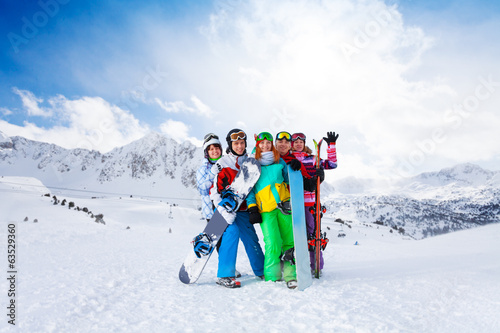 Five friends standing with snowboards