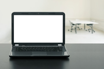 laptop with blank screen on wooden table in the office