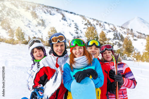 Five smiling friends with snowboards