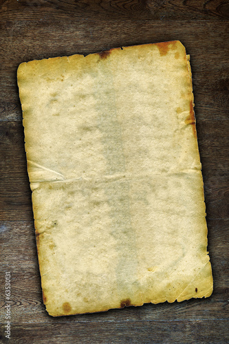 Old grunge paper on brown wooden surface with natural patterns