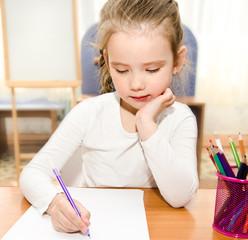 Little girl is writing at the desk  in preschool