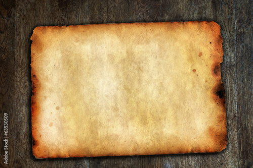 Old vintage paper on brown wooden surface with natural texture