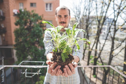 handsome stylish man holding basil plant