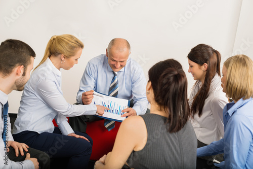 Business Team Discuss Graph Sitting Meeting Room
