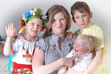 Young mother with three children in national Ukrainian suits