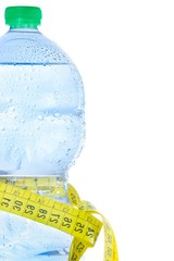 bottle with water, drops and measuring tape, concept of fitness