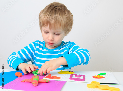 little boy playing with clay dough