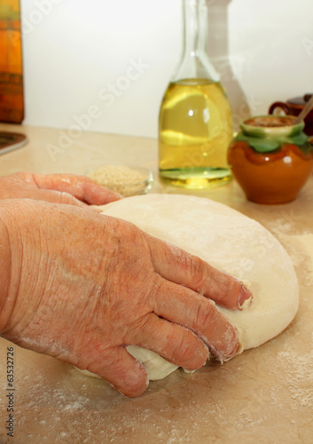 Female hands kneading dough.
