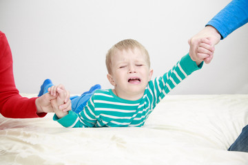 divorced parents holding sad child separately