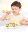Cute little boy is eating vegetable salad