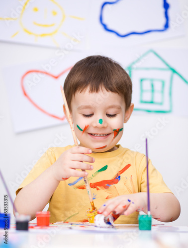 Portrait of a cute boy playing with paints