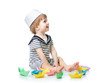 Cute baby boy with sailor hat  playing with paper boats