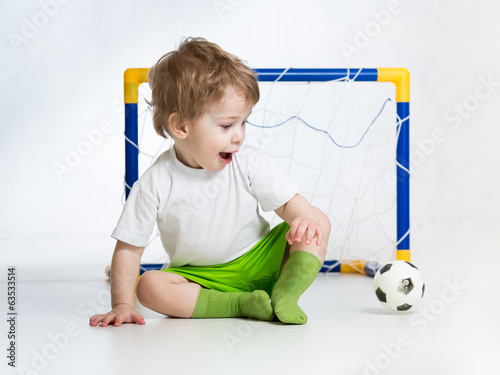 kid football player looking at soccer ball