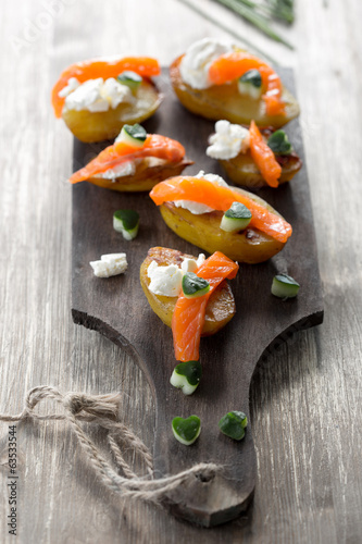appetizer with salmon,baked potatoes and curd cheese.