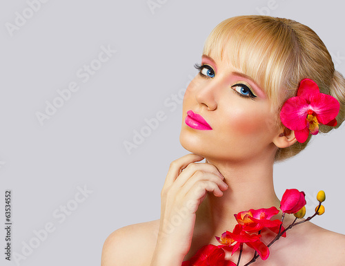 Beautiful blonde girl with flower on grey background
