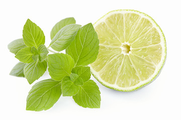 Limes with a mint branch on the isolated white background