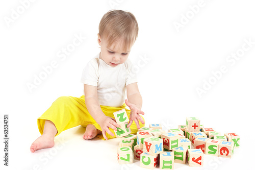 The small child builds a tower of cubes