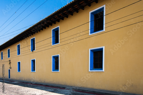 Yellow painted townhouse with blue windows